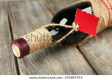 Red wine bottle wrapped in burlap cloth on wooden planks background - stock photo