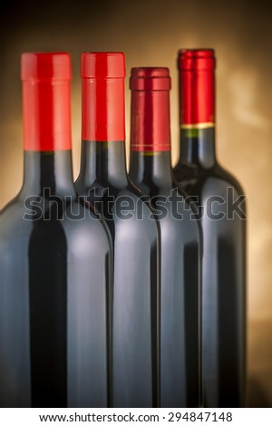 Red wine bottles stacked vertically - stock photo