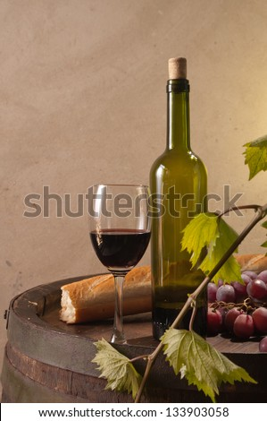 Red wine, bread and grapes in a still life setup.