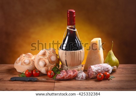 Red wine, bread, cheese and salami on the wooden table