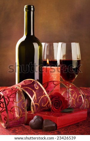 Red wine, candle and chocolate hearts, still life - stock photo