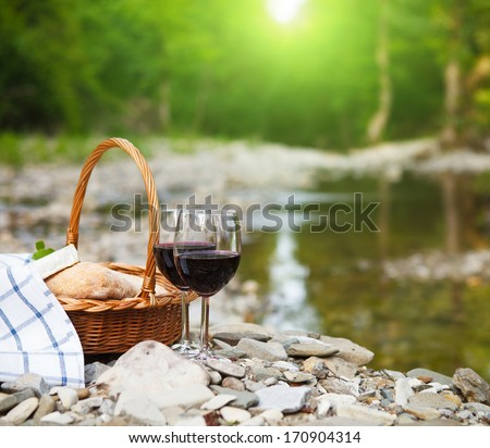 Red wine, cheese and bread served at a picnic. Mountain river background - stock photo