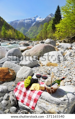 Red wine, cheese and grapes served at a picnic. Verzasca valley, Switzerland - stock photo