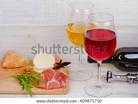 Red wine, cheese, basil and prosciutto on white wooden background - stock photo