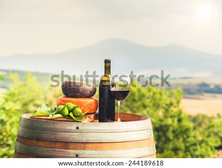 Red wine, cheese, figs on a wooden barrel in the background of the Tuscan landscape, Italy - stock photo