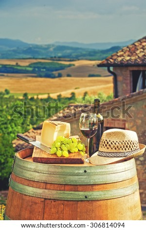 Red wine, cheese, grapes and a straw hat on a wooden barrel on the background of the Tuscan landscape, Italy