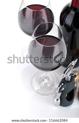 Red wine, corks and corkscrew. Isolated on white background, closeup, focus on glasses. - stock photo