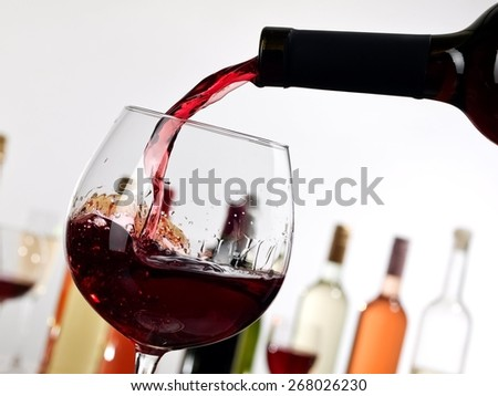 Red wine flow in a glass, close up - stock photo