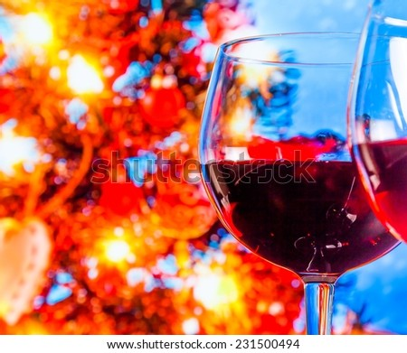 red wine glass against blur lights tree background, christmas atmosphere - stock photo