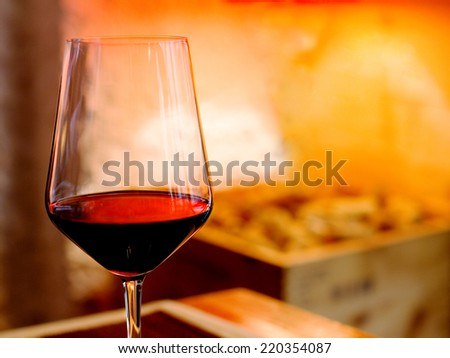 red wine glass against red warm background