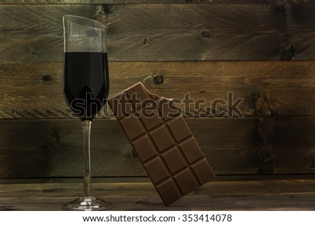 Red wine glass and bitten chocolate bar on vintage wooden background. Concept for unhealthy food and life style - stock photo