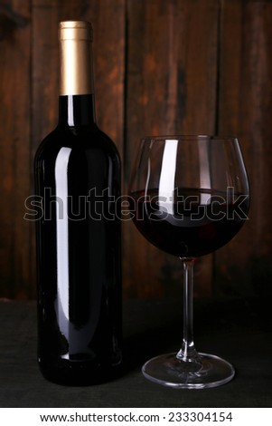 Red wine glass and bottle of wine on wooden background - stock photo