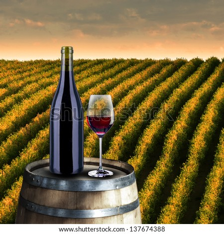 Red wine glass and bottle on wood barrel with vineyard background