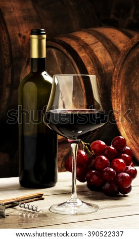 red wine glass and bottle over old barrelsa background