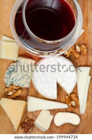 red wine glass and portion of sliced cheeses on wood plate - stock photo