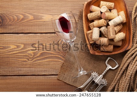 Red wine glass, corks and corkscrew on wooden table background with copy space - stock photo