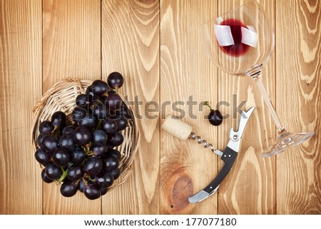 Red wine glass, corkscrew and grape on wooden table background - stock photo
