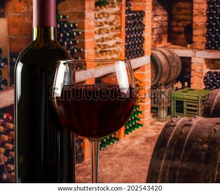 red wine glass near bottle in the old wine cellar background with barrels with space for text - stock photo