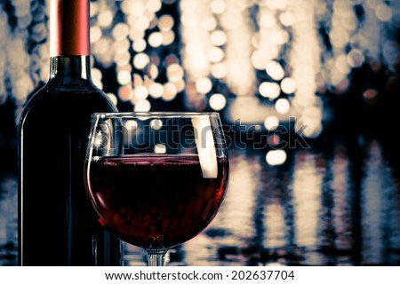 red wine glass near bottle with light bokeh in background - stock photo