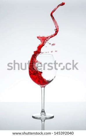 Red wine glass splash on gray white background - stock photo