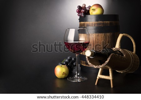 Red wine glass with bottle in sraw prop and old wooden barrel surrounded by fruits: vine and apples - stock photo