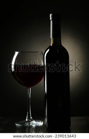 Red wine glass with bottle on black background