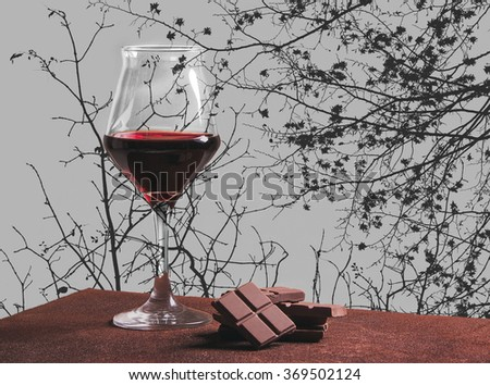 Red wine glass with chocolate and autumn tree branches - stock photo