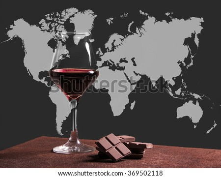 Red wine glass with chocolate and world map - stock photo