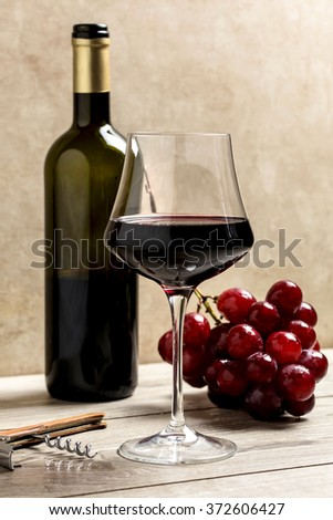 red wine glass with corkscrew, bottle and red grapes bunch