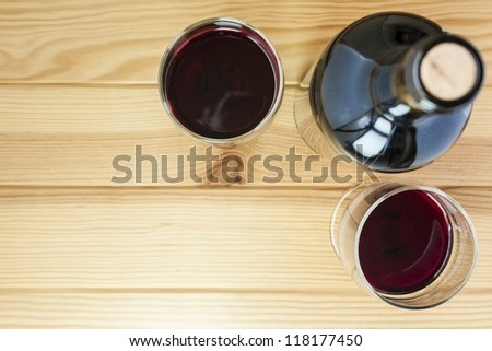 red wine glasses and bottle over pine wood table - stock photo