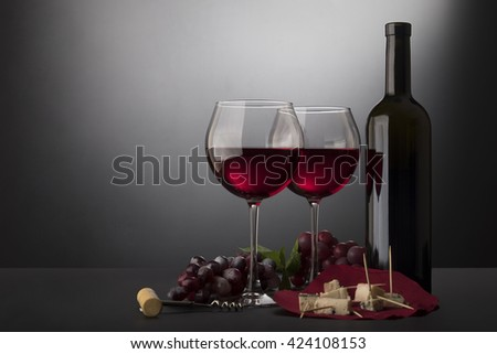 Red wine glasses, bottle of wine, cheese and vine isolated on black gradient with copy space