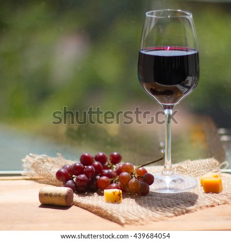 Red wine, grape and cheese on wooden table