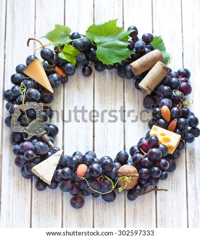 Red wine grape wreath decorated cheese, nuts and old corkscrew hanging on wooden board with place for text or invitation. Vintage style.
