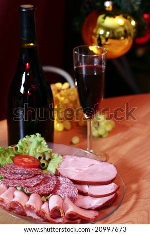 Red wine, grapes and meat on a New Year's background. - stock photo