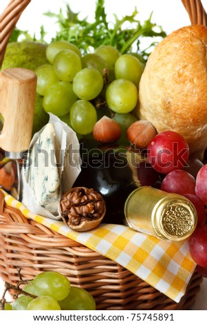 Red wine, grapes, nuts, cheese and bread on a wicker basket.