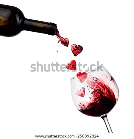 Red wine hearts pouring in a glass - stock photo