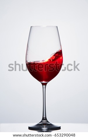 Red wine in a crystal pure wineglass showing waves against light background.