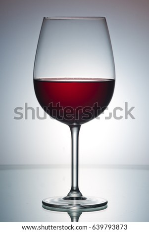 Red wine in a glass. A single glass. Colorful background. Wine-making. Reflection from a glossy surface.