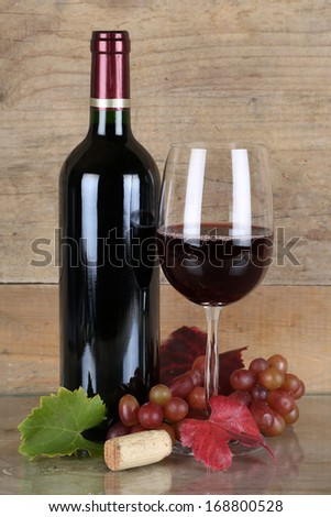 Red wine in bottle and wineglass in front of a wooden background