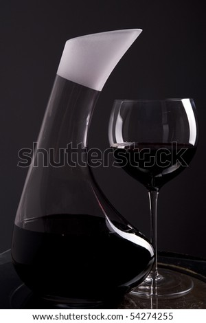 Red wine in decanter with a full glass with wine beside isolated on dark background - stock photo