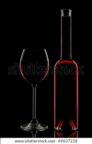 Red wine in glass and bottle on black background close up
