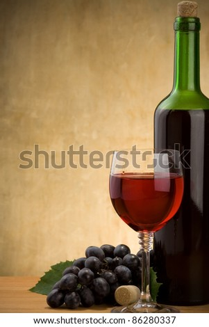red wine in glass and bottle on wood background - stock photo