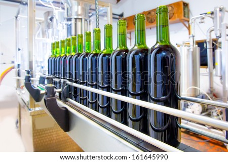 red wine in glass bottling machine at winery - stock photo