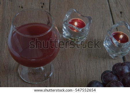 red wine in glass for a romantic and  candle on wooden table.