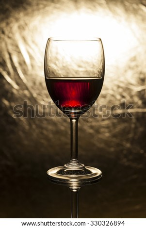 Red wine in glass on a gold background. - stock photo