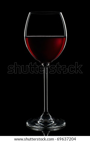 Red wine in glass on black background close up
