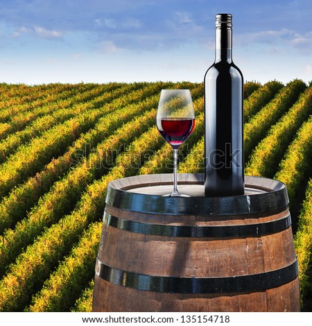 Red Wine in glass on wood barrel with vineyard background
