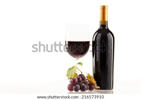 Red wine in glass with bottle and wine grapes - stock photo
