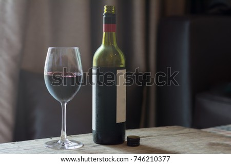 Red wine in glass with bottle on brown wooden table.