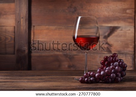 Red wine in glass with grape on wooden background - stock photo